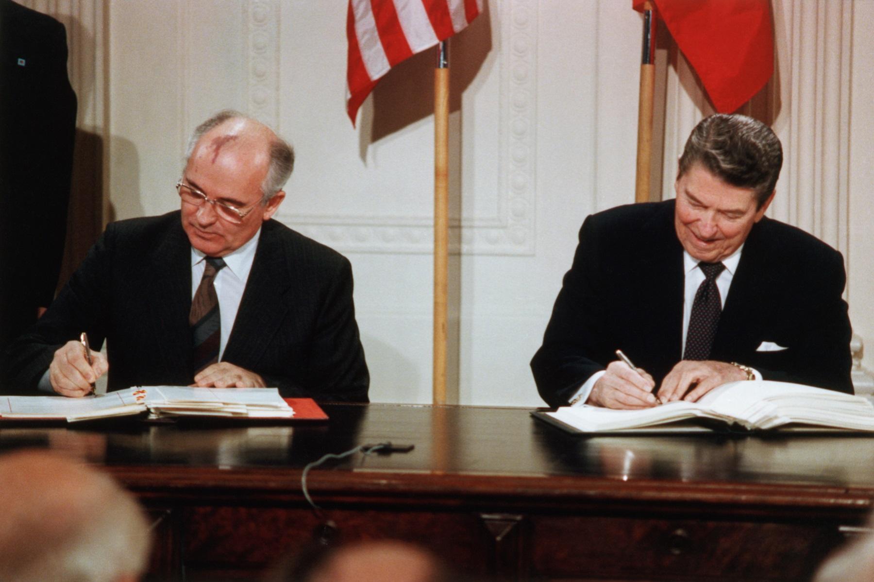 الرئيس الأميركي رونالد ريغان والرئيس السوفياتي ميخائيل غورباتشيف يوقّعان معاهدة الصواريخ النووية متوسطة المدى، 8/12/1987 (غيتي)