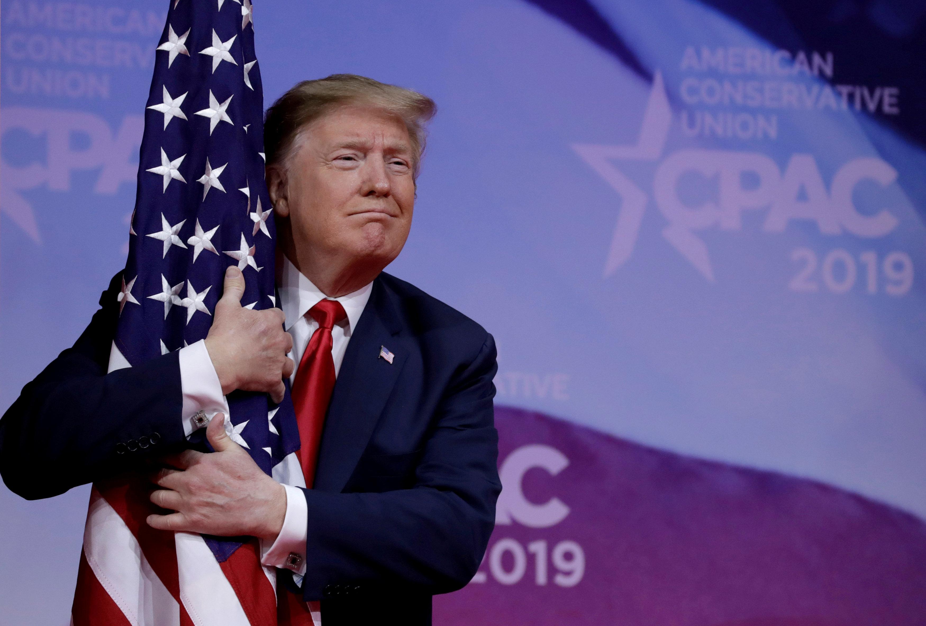الرئيس دونالد ترمب معانقاً العلم الأميركي (رويترز)