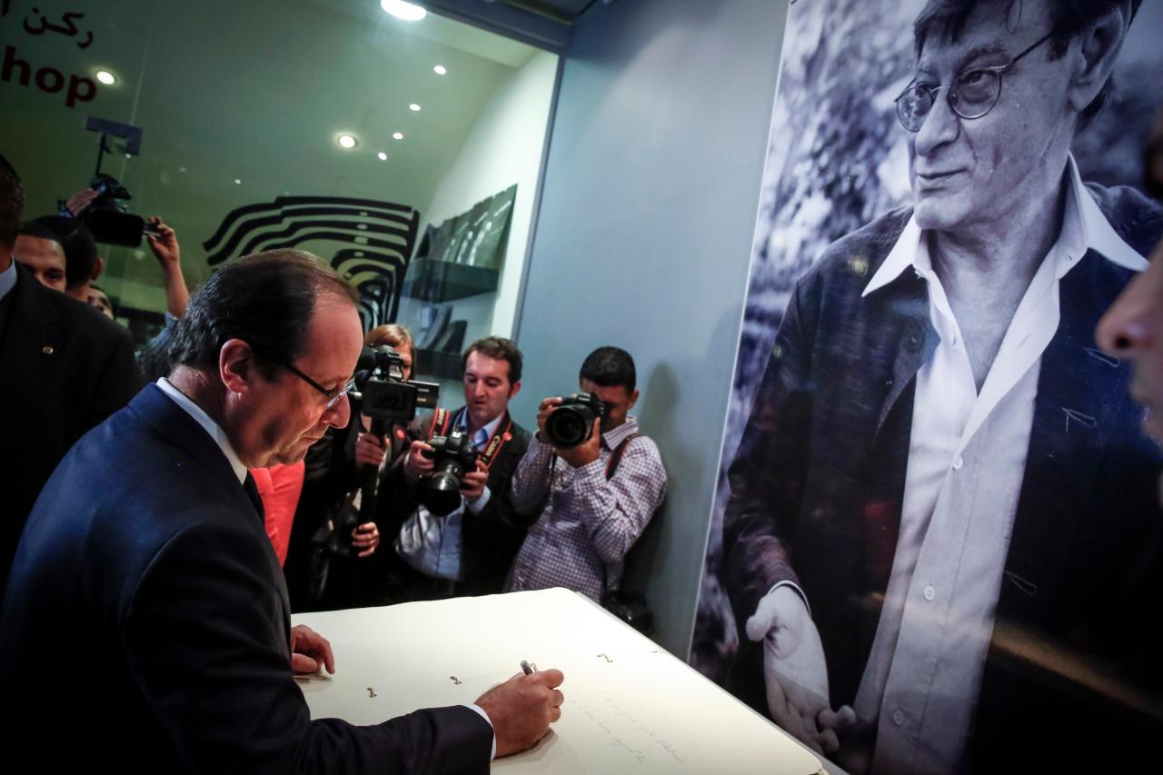 """الرئيس الفرنسي السابق فرانسوا هولاند أمام صورة الشاعر الراحل محمود درويش أثناء زيارته لمتحفه في """"رام الله"""" بالضفة الغربية. 18 نوفمبر(تشرين الثاني) 2013. (أ.ف.ب)"""