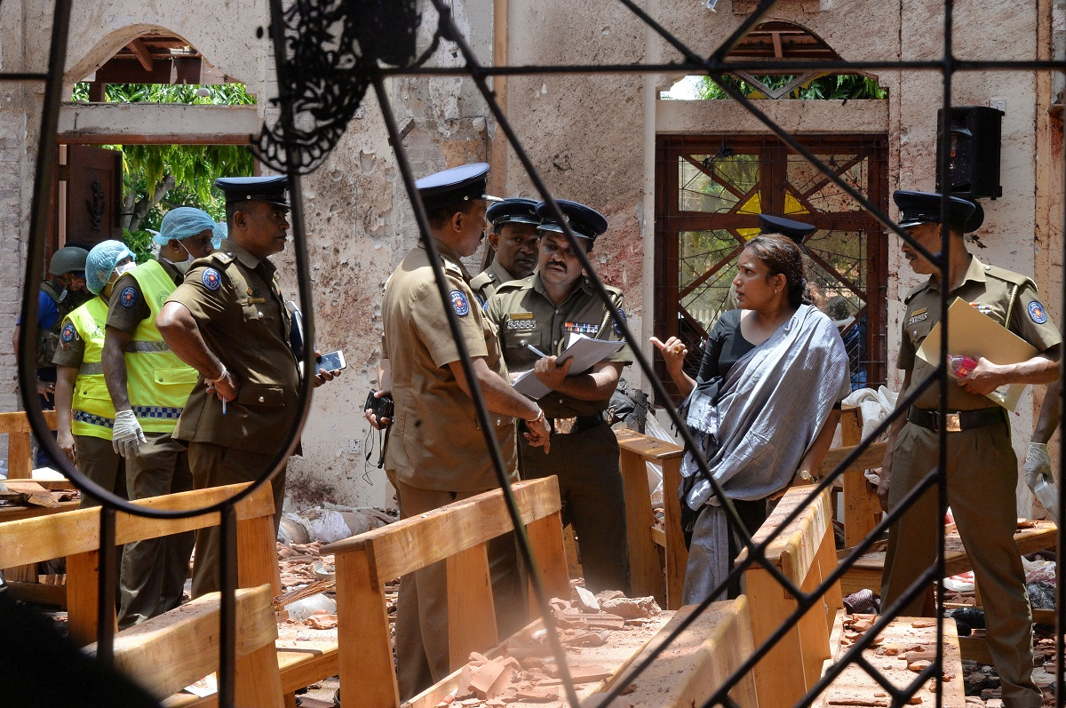 الشرطة السريلانكية تعاين موقع انفجار إحدى الكنائس بالعاصمة كولومبو (أ.ب)