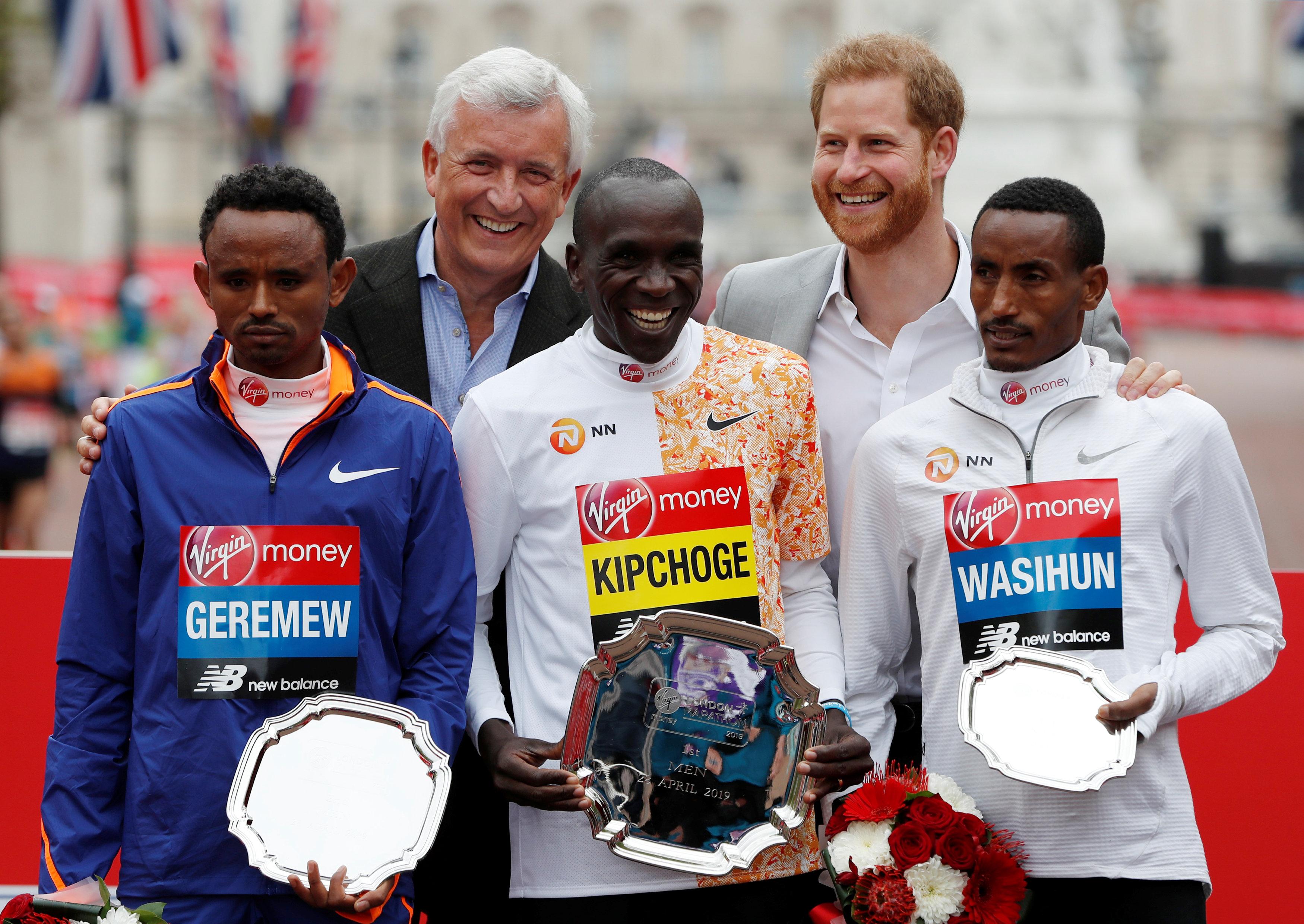 الكيني إليود كيبتشوج يحتفل بالفوز في سباق النخبة للرجال مع الكأس والأمير البريطاني هاري، 28 أبريل 2019  (رويترز)