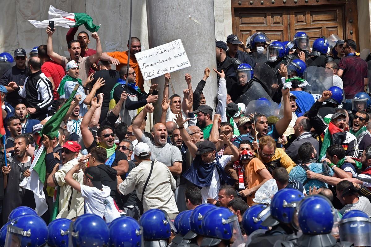 """جزائريون يرفعون شعار """"لا للانتخابات"""" في المسيرة 13 في العاصمة (أ.ف.ب)"""