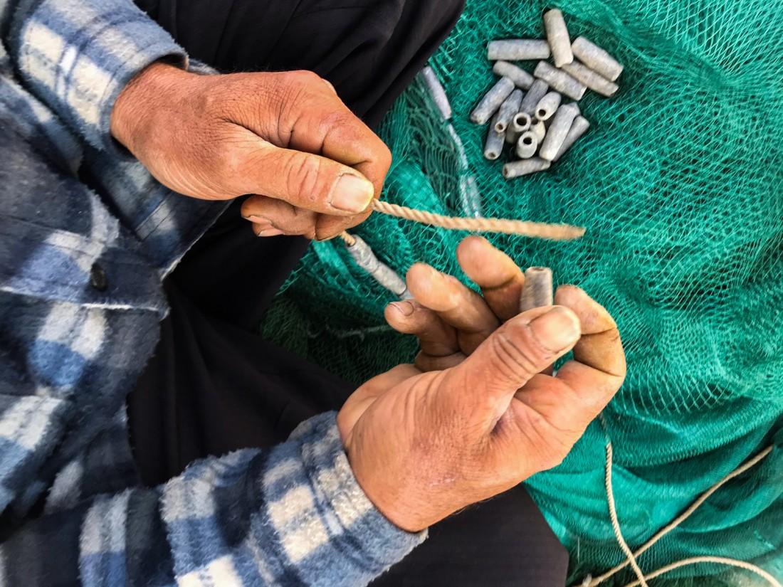 تطلب حياكة شباك الصيد جهداً وصبراً (مريم أبو دقة)