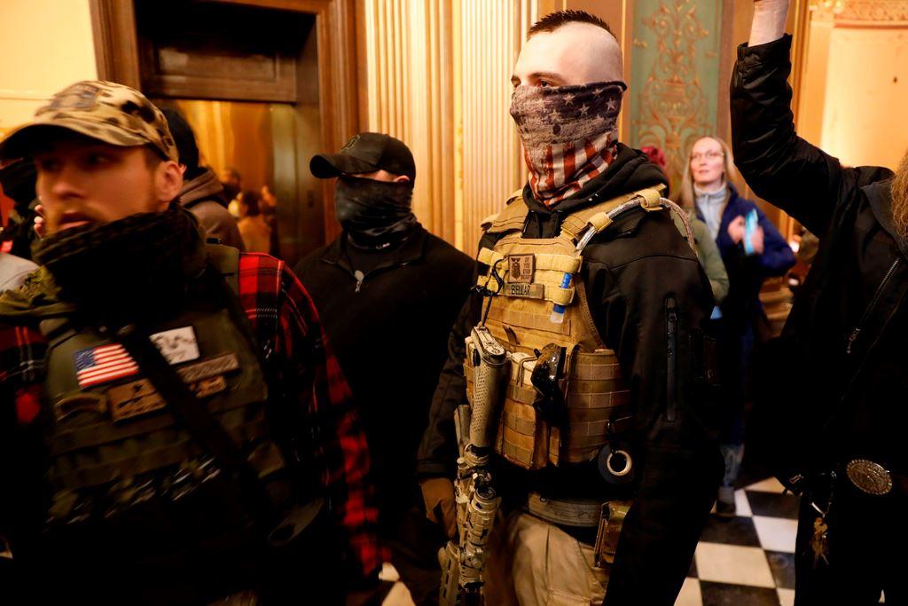 أميركيون مسلحون رافضون للإغلاق بسبب كورونا يحاولون دخول مقر الحكومة في ميشيغان (أ.ف.ب)