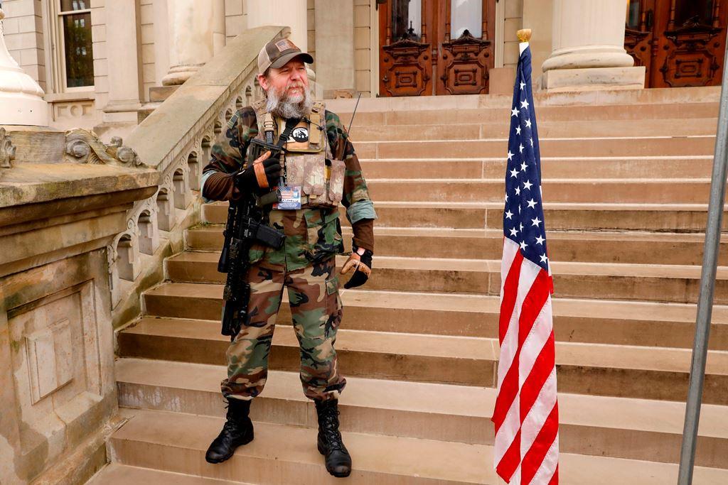"""متظاهر أميركي مسلح من ميشيغان يقف أمام مبنى الحكومة """"الكابيتول """"لمنع تمديد الإغلاق بسبب كورونا (أ.ف.ب)"""