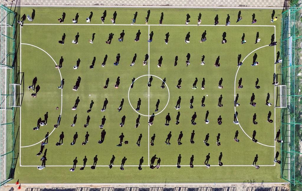 لا ينتظر هؤلاء المشاركة في مباراة لكرة القدم بل يطبقون التباعد الاجتماعي للخضوع لفحص كورونا (أ.ب)
