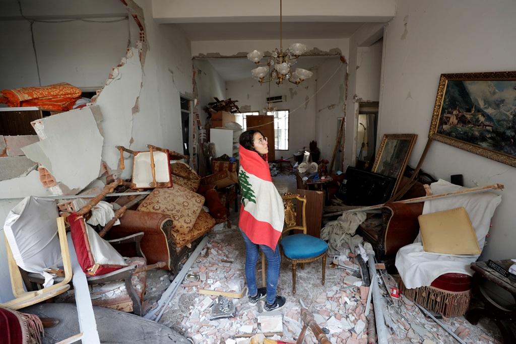 مواطنة تتفقد منزلها الذي تعرض للدمار جراء انفجار بيروت (أ.ب)