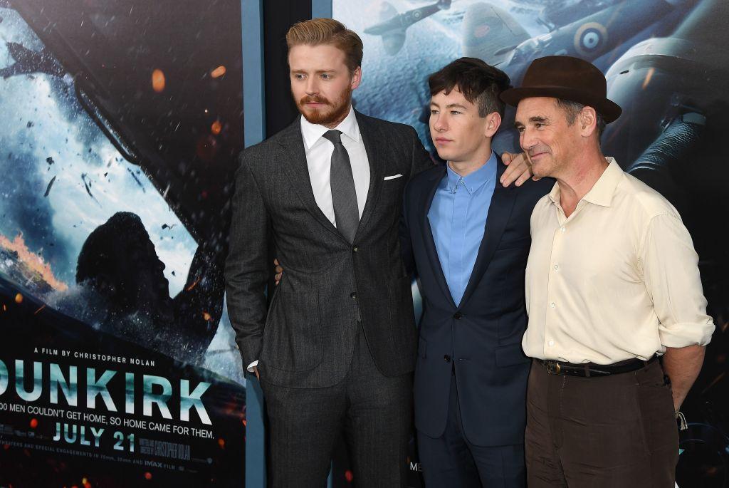 الممثلون في فيلم دانكيرك وخلفهم الملصق الإعلاني للفيلم (غيتي)