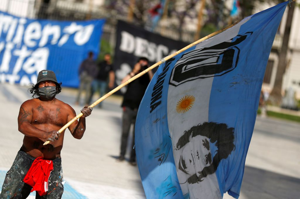 أرجنتيني يرفع علم مارادونا في شوارع بيونس آيرس (رويترز)