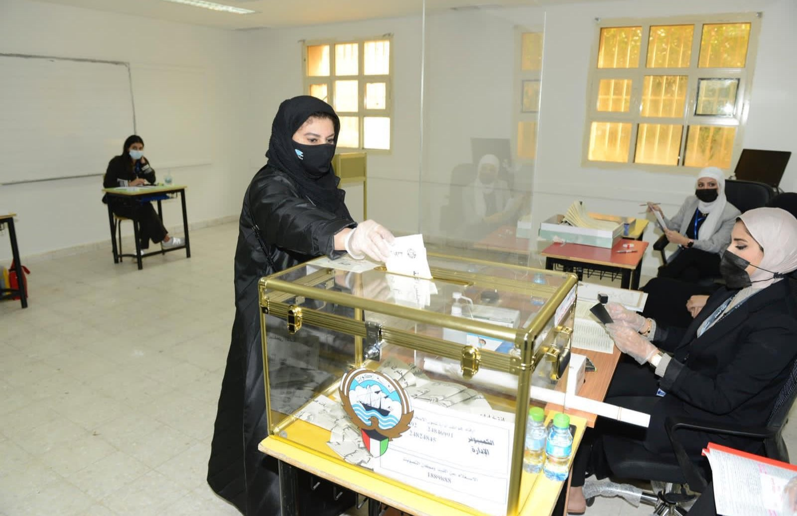 سيدة كويتية ترمي ببطاقة مرشحها الانتخابي في صندوق الاقتراع. (وزارة الإعلام الكويتية)