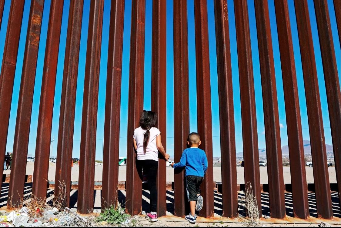 طفلان ينظران من خلال الجدار الفاصل بين الولايات المتحدة والمكسيك .(غيتي).jpg