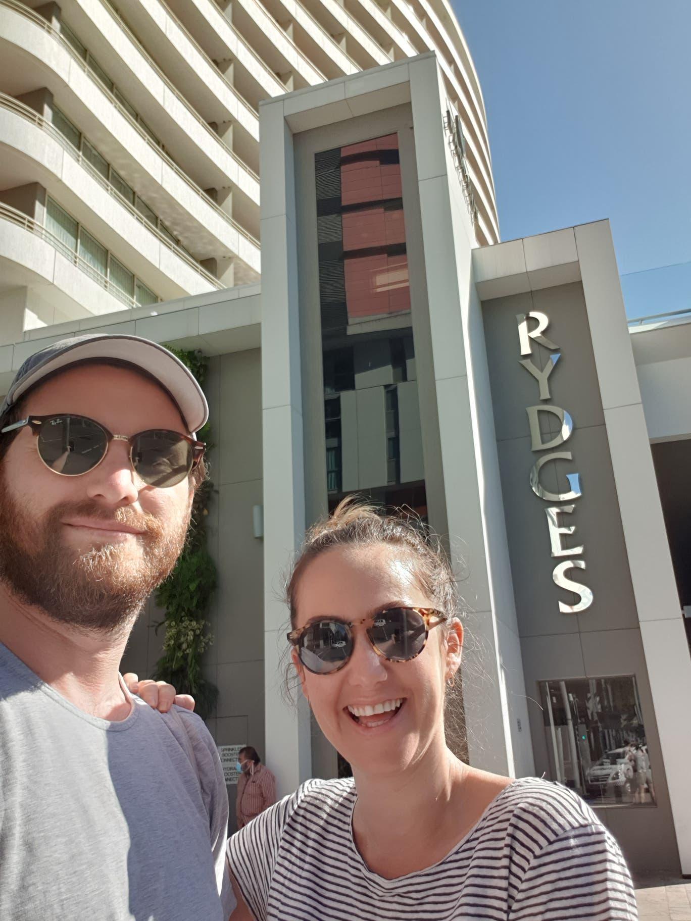 كلوي كان وشريك حياتها وخلفهما الفندق حيث عزلا لمدة أسبوعين لدى عودتهما إلى أستراليا(عن كلوي كان)