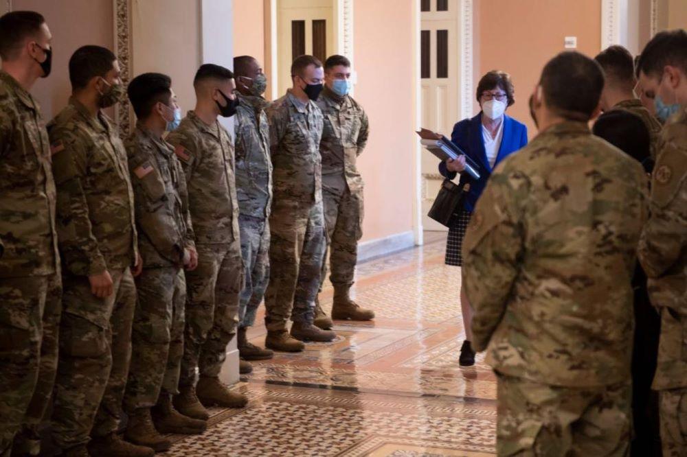 السيناتورة سوزان كولينز تعبر بين جنود الحرس الوطني في طريقها إلى جلسة محاكمة ترمب (أ.ف.ب).jpg