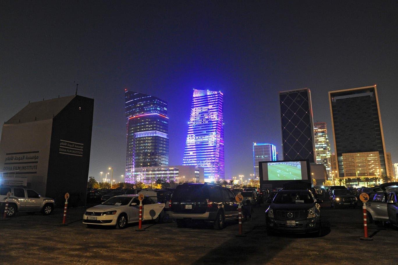مشجعون يتابعون مباراة لكرة القدم في الهواء الطلق في الدوحة (أ ف ب وغيتي)