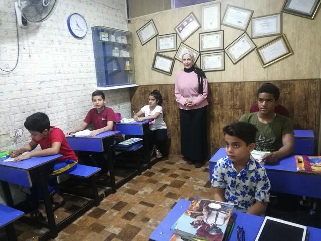 المتطوعة سلوى محمد وهي تقوم بمساعدة الاطفال في أنجاز واجباتهم.jpg