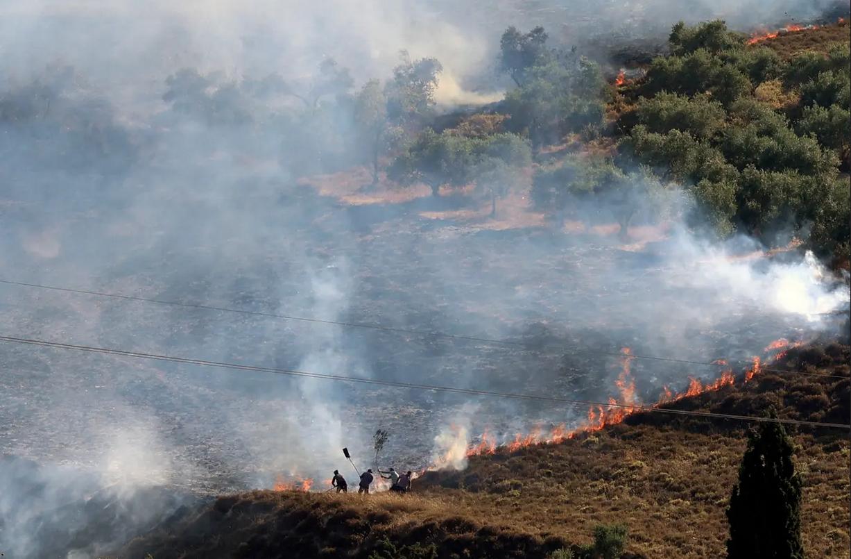 فلسطينيون يخمدون حريقاً في حقل حول قرية بورين، إلى الجنوب من نابلس في الضفة الغربية المحتلة
