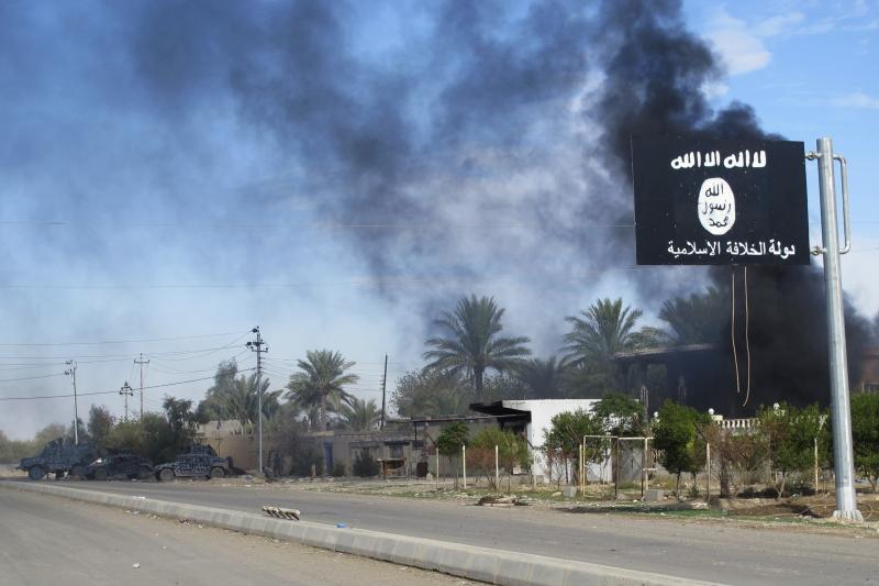 """العلم الأسود المميز لتنظيم """"داعش"""" معلقاً عند مدخل محافظة ديالى في العراق عام 2014"""